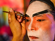 """26 FEBRUARY 2018 - BANGKOK, THAILAND: A performer gets help with his makeup before a Chinese Opera at the Phek Leng Shrine in the Khlong Toey section of Bangkok. The shrine traditionally hosts a Chinese Opera just after the end of Lunar New Year festivities. Thailand is home to the largest population of overseas Chinese in the world, and Chinese cultural practices, like Chinese opera, called """"ngiew"""" in Thailand, are popular. Many of the performers are ethnic Thais who don't speak Chinese. They learn their lines phonetically.    PHOTO BY JACK KURTZ"""