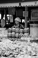 A woman selling coconuts and pudding at the market on the waterfront of kota kinabalu.