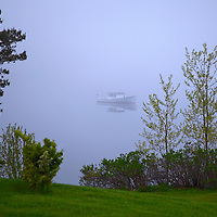 North America, Canada, Nova Scotia, Guysborough. Boat floating in fog iChedabucto Bay.