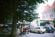 People sitting outside at tables under shade of tree, Cafe le Menestrel, Carcassonne, France 1973