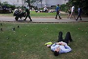 Young businessman sleeps during a lunchtime break on the grass in St. Paul's cathedral churchyard.