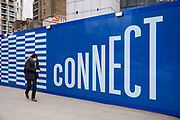 People pass a hoarding with the word connect surrounding the now closed down Elephant and Castle shopping centre which is due for demolition on 5th March 2021 in London, United Kingdom. The area is now subject to a master-planned redevelopment budgeted at £1.5 billion. A Development Framework was approved by Southwark Council in 2004. It covers 170 acres and envisages restoring the Elephant to the role of major urban hub for inner South London.