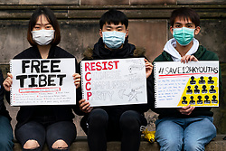 Edinburgh, Scotland, UK. 10 October 2020. Protestors from the Hong Kong Pro-democracy movement staged a demonstration at St Giles Cathedral today. The protestors, all Hong Kong nationals studying at Scottish universities, were protesting against China's persecution of ethnic minority Uyghurs and the new national Security laws imposed on Hong Kong by China. The protestors wore facemarks not only as a health precaution but also to maintain anonymity.The National Security Law means Hong Kong nationals can be persecuted for protesting anywhere in the world. A mainland Chinese couple in an apartment opposite heckled the protestors and filmed them. This video could in theory be passed to the Chinese authorities and have grave consequences for the protestors if they were to be recognised. Iain Masterton/Alamy Live News