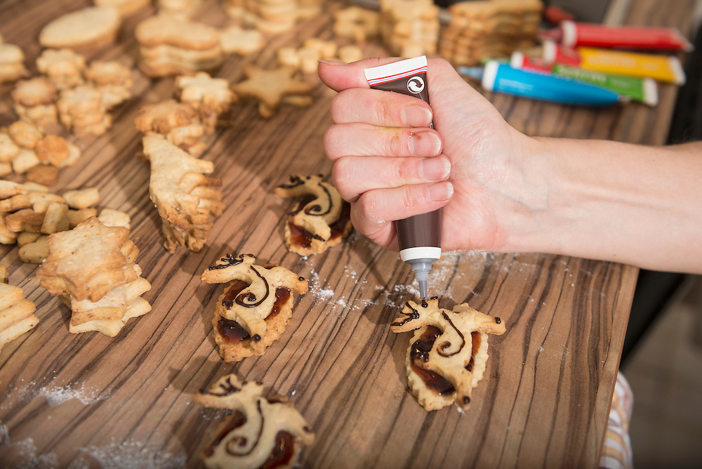 Close-up of a woman decorating reindeer shaped cookies, Munich, Bavaria, Germany