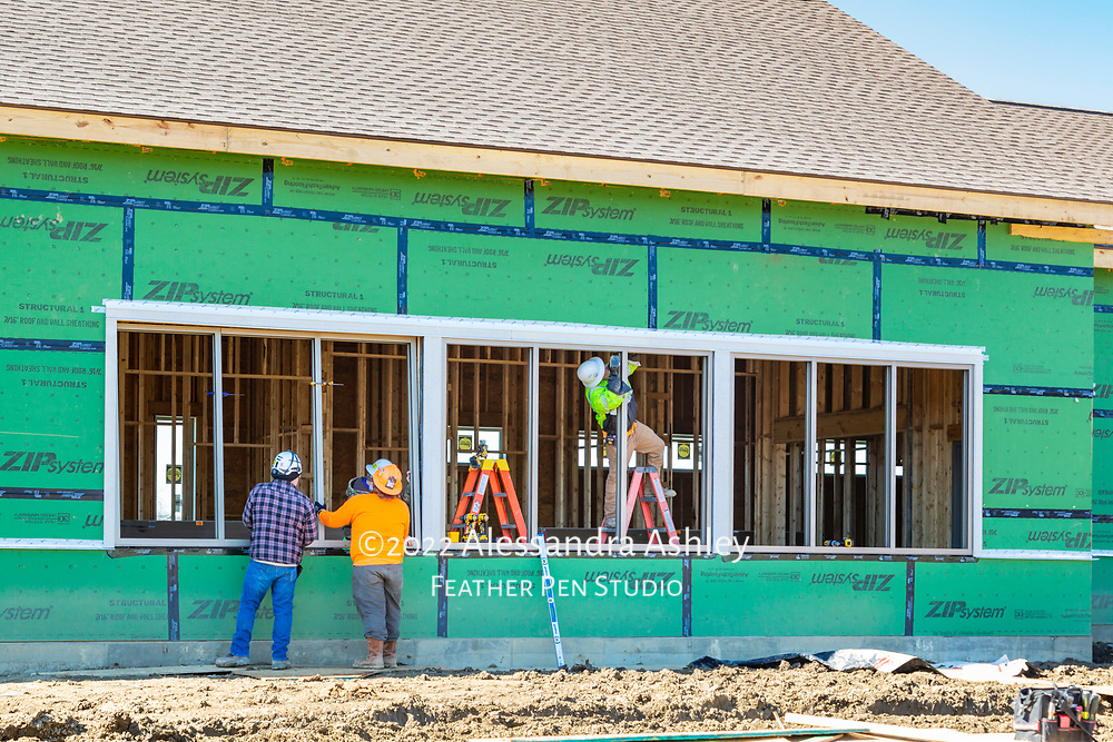 Crew installs frames for gymnasium windows at construction site of new physical therapy and wellness center building.