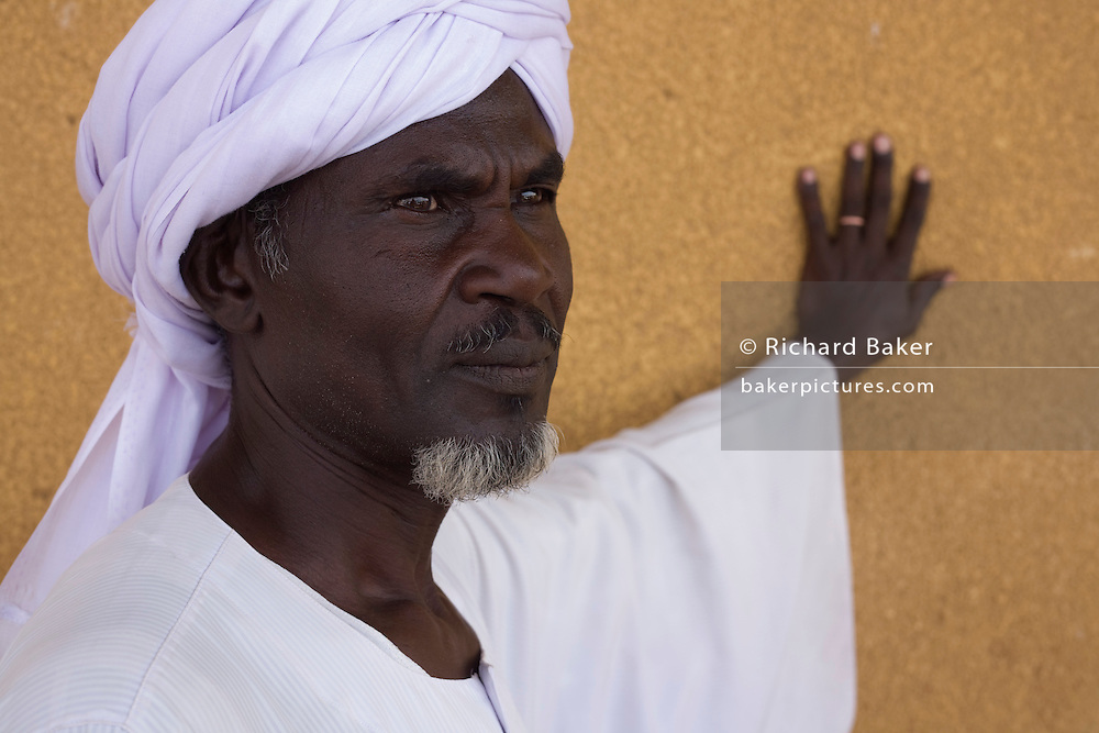 Official stands in the shade at the 4 sq km Abu Shouk refugee camp, which is (disputedly) home to 38,000 displaced persons, on the outskirts of Al Fasher, North Darfur, Sudan.