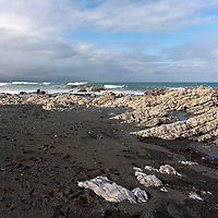Stone formations at the black sand beach of Kaikoura. Kaikoura is one of the famoust whale watching sites in the world.