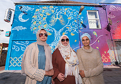 © Licensed to London News Pictures; 23/09/2021; Bristol, UK. MANAZZAR SIDDIQUE, SAFINA KHAN, and AUMAIRAH HUSSAN, members of an all-female Muslim street art collective called Peace of Art have painted a mural on the side of the Thali restaurant in Easton, Bristol, to highlight the dangerous levels of air pollution in the area. The mural stretches the length of the building with a tree showing a pair of lungs with the left side healthy and the right side affected by pollution from the city and with the word 'Breathe' on the end.  Photo credit: Simon Chapman/LNP.