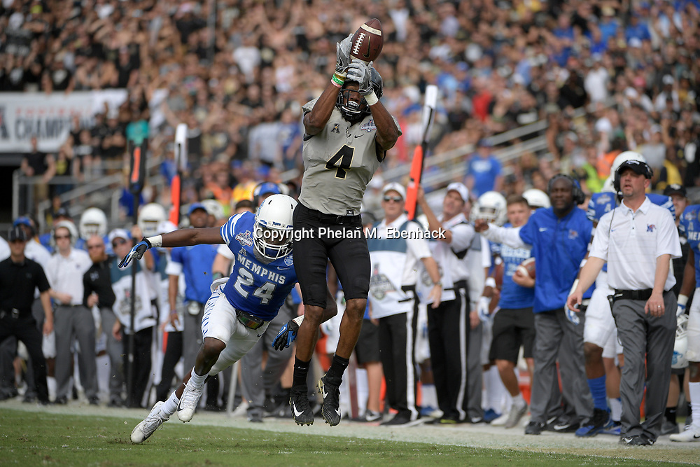 Central Florida wide receiver Tre'Quan Smith (4) misses a catch in front of Memphis defensive back Tito Windham (24) during the first half of the American Athletic Conference championship NCAA college football game Saturday, Dec. 2, 2017, in Orlando, Fla. (Photo by Phelan M. Ebenhack)
