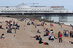 © Licensed to London News Pictures. 07/07/2014. Brighton, UK. people on Brighton beach. South Coast recovers today with temperatures around 24C after a day with rain and clouds on Saturday. Photo Credit: Hugo Michiels/LNP