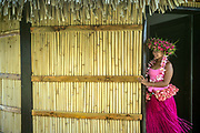 Traditional performers dress and prepare to dance for passengers disembarking in the port of Uturoa on the Island of Raiatea, French Polynesia.