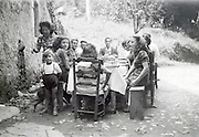 large family eating gathering outside in a rural environment 1950s 1960s