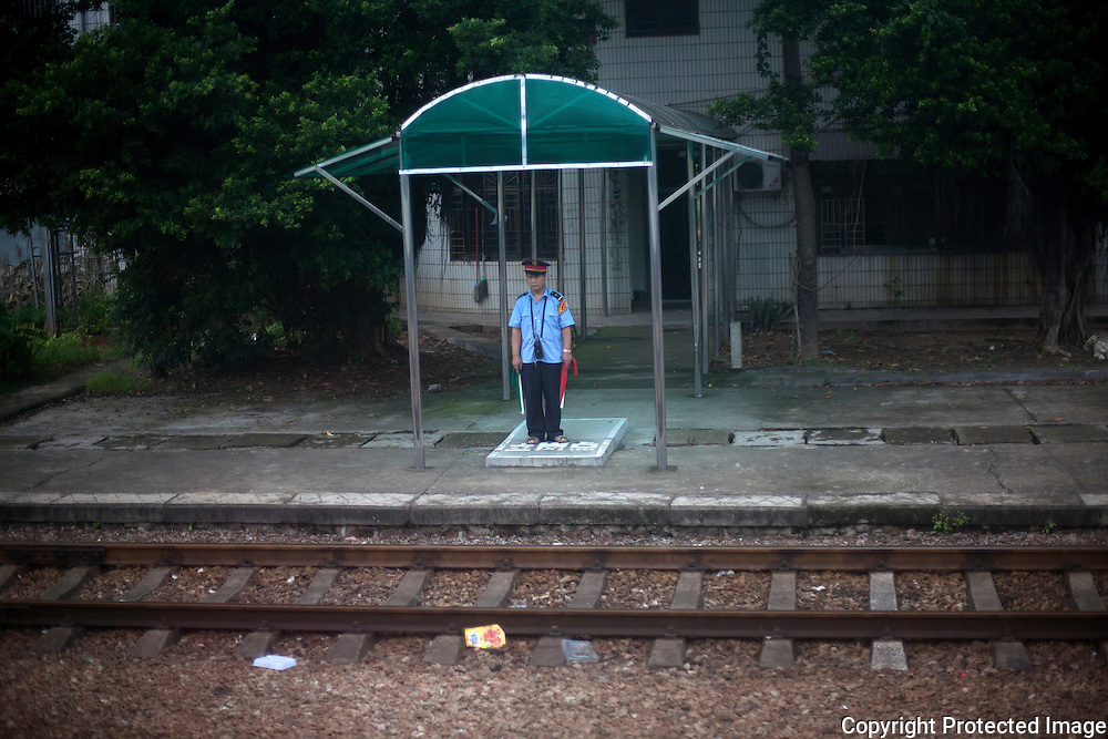 A lone station guard mans his post along the Kunming to Hong Kong train route.