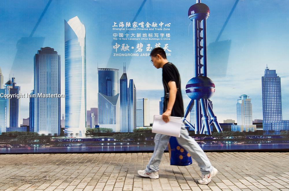Man walks past billboard advertising modern property development in Pudong financial district of Shanghai