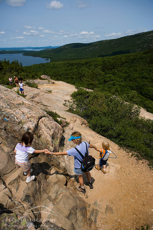 A woman and her young children hiking on the South Bubble in Acadia National Park Maine USA