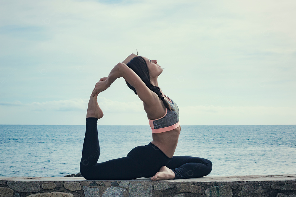 Young woman doing yoga at the sea One-Legged King Pigeon Pose