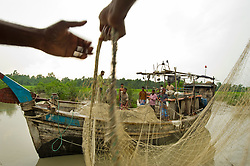 """Women and children from the fishing village of South Tetulbarian in Barguna Sadar upazila  in Bangladesh gather to watch their husbands and fathers and brothers prepare the boat to go out to sea, October 2o, 2010 . Its a dangerous job and everyone knows it could be the last time they see their loved ones. There is no guarantee that they will return home. Because of climate change, the seas are getting more violent, less predictable and boats are capsizing more frequently. Twenty percent of the women in this village are widows because so many have lost their husbands in the seas. Coastal and fishing populations are particularly vulnerable and Fishing communities in Bangladesh are subject not only to sea-level rise, but also flooding and increased typhoons. Erosion as a result of stronger and higher tides, cyclones and storm surges is eating away Bangladesh's southern coast.  Yet the largely fishing community cannot live without the sea. """"We only know how to catch fish,"""" say the fishermen. ( Ami Vitale)"""