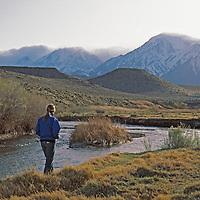 A woman walks beside the Owens River.