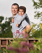 Dad with son on his back for family portrait session at Acton Arboretum.
