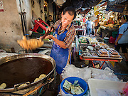 29 JUNE 2015 - BANGKOK, THAILAND: A vendor makes patongos, a Chinese style doughnut that has also been compared to a Chinese beignet, in Bang Chak Market in Bangkok. The Bang Chak Market serves the community around Sois 91-97 on Sukhumvit Road in the Bangkok suburbs. About half of the market has been torn down, vendors in the remaining part of the market said they expect to be evicted by the end of the year. The old market, and many of the small working class shophouses and apartments near the market are being being torn down. People who live in the area said condominiums are being built on the land.      PHOTO BY JACK KURTZ