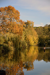 Woman paddleboarding on the River Wensum, Norwich UK November 2019