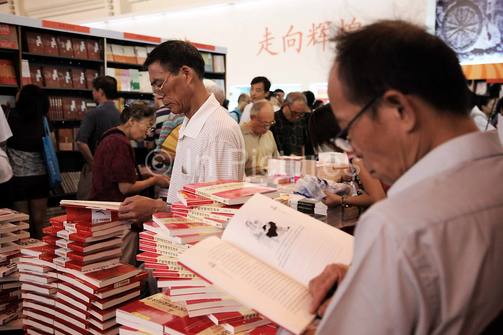 Visitors sort through books on offer at a book fair in Shanghai, China on 16 August 2009.  China may appeal a recent World Trade Organization (WTO) ruling that its limits on the sale of books, films and music from the US are unfair.