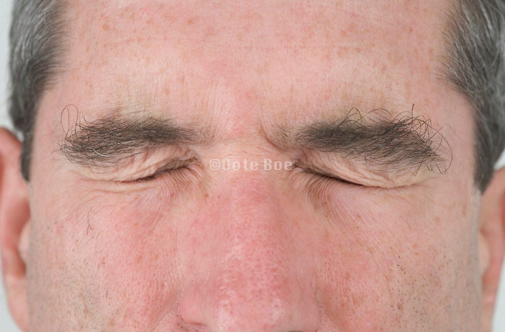 close up of a middle aged man's face with his eyes tightly closed