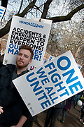 Tens of thousands of health workers, activists and members of the public protested against austerity and cuts in the NHS National Health Service on March 4th 2017 in London, United Kingdom. A young man with a beard holds one placard saying One fight we all unite, and another saying Hands off HRI Halifax Royal Infirmary,