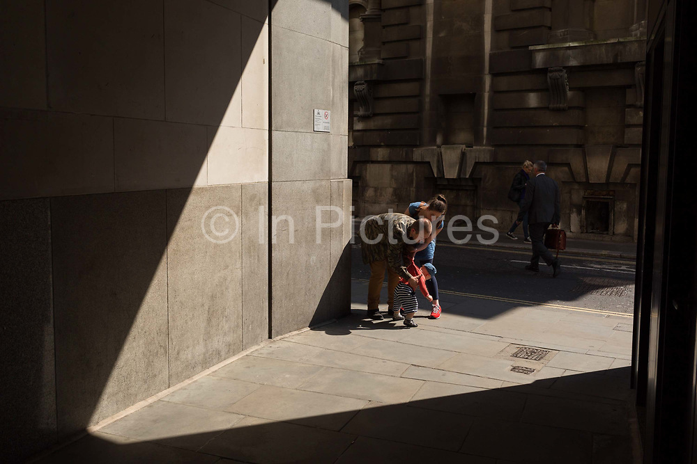 The parents of a small child in Lombard Street in the City of London, the capitals financial district aka the Square Mile, on 15th May 2018, in London, UK.