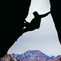A rock climber 'boulders' in the Buttermilk Rocks below Basin Mountain.
