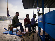 11 MARCH 2013 - ALONG HIGHWAY 13, LAOS: Men sit on the bow of a Mekong River ferry during a river crossing. The Mekong River ferries are disappearing as bridges across the river are completed and roads along the river are paved. The paving of Highway 13 from Vientiane to near the Chinese border has changed the way of life in rural Laos. Villagers near Luang Prabang used to have to take unreliable boats that took three hours round trip to get from the homes to the tourist center of Luang Prabang, now they take a 40 minute round trip bus ride. North of Luang Prabang, paving the highway has been an opportunity for China to use Laos as a transshipping point. Chinese merchandise now goes through Laos to Thailand where it's put on Thai trains and taken to the deep water port east of Bangkok. The Chinese have also expanded their economic empire into Laos. Chinese hotels and businesses are common in northern Laos and in some cities, like Oudomxay, are now up to 40% percent. As the roads are paved, more people move away from their traditional homes in the mountains of Laos and crowd the side of the road living off tourists' and truck drivers.    PHOTO BY JACK KURTZ