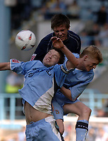 Photo. Glyn Thomas. <br /> Coventry City v Brighton and Hove Albion. <br /> Coca Cola Championship. 02/04/2005.<br /> Brighton's Adam Virgo (C) climbs higher than Stephen Hughes (L) and Claus Jorgensen.