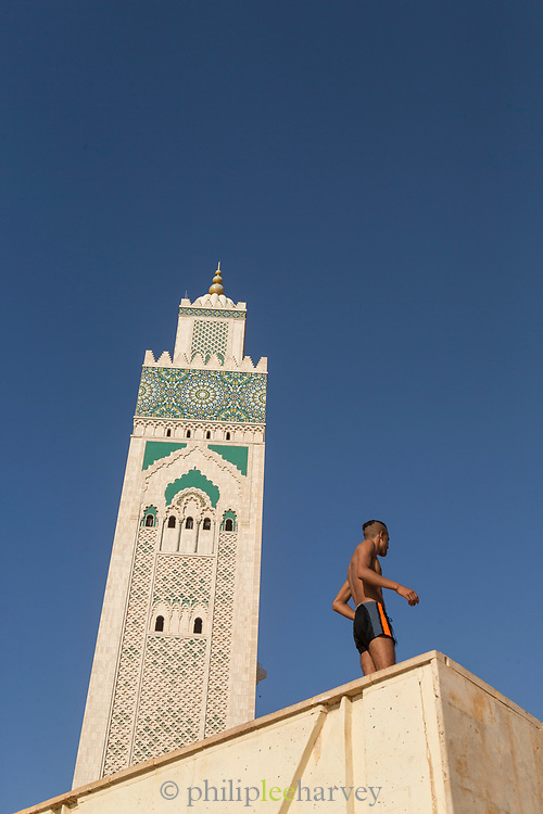 Low angle view of man wearing swimming trunks about to jump into sea nearby Hassan II Mosque in Casablanca, Morocco