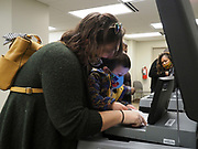 Owen Smith, age 3, helps his mom Amanda Smith place her ballot in the optical scanner as an election official looks on.