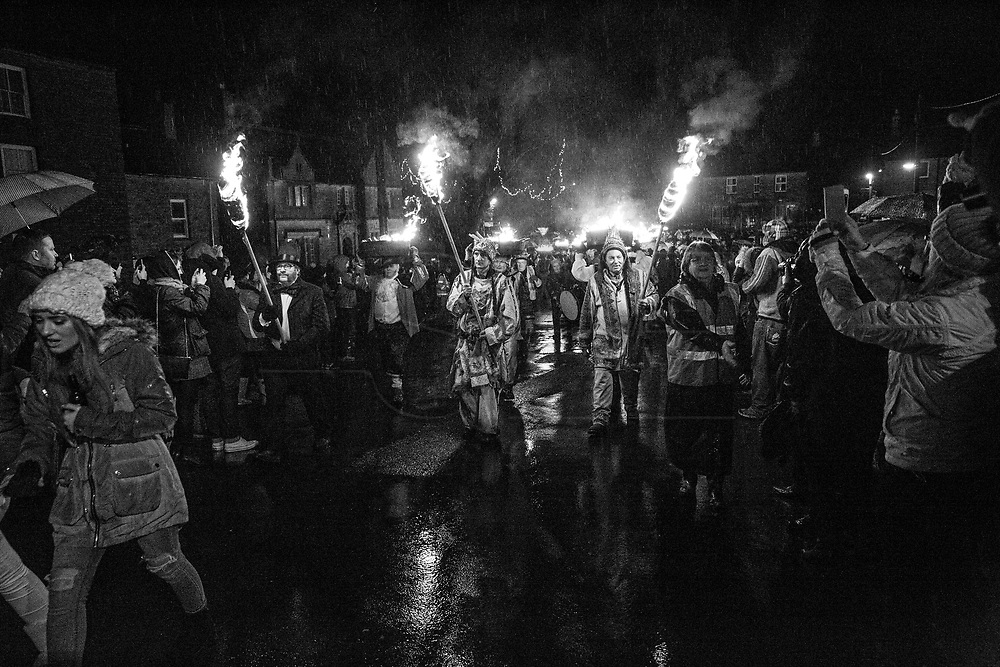 """Allendale Town, New Year's Eve 2017. Men are carrying burning barrels filled with tar, sawdust, kindling and paraffin on their heads.<br /> The Tar Barl Festival has been Allendale's way of welcoming the new year for at least 160 years.<br /> The normally quiet village heaves with people - locals, visitors and the barrel-carrying """"guisers"""" wearing fancy dress or a disguise. <br /> A fiery procession swarms round the Northumberland village, returning to the square just before midnight to throw its barrels on to the waiting bonfire, setting it alight."""
