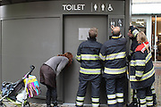 Brandweermannen zoeken naar een manier om de deur van een openbaar toilet te openen om een meisje te bevrijden. De moeder kalmeert ondertussen haar kind.<br /> <br /> Firemen are trying to open a public toilet, where a young girl has been locked up. The mother (right) is trying to calm her child.