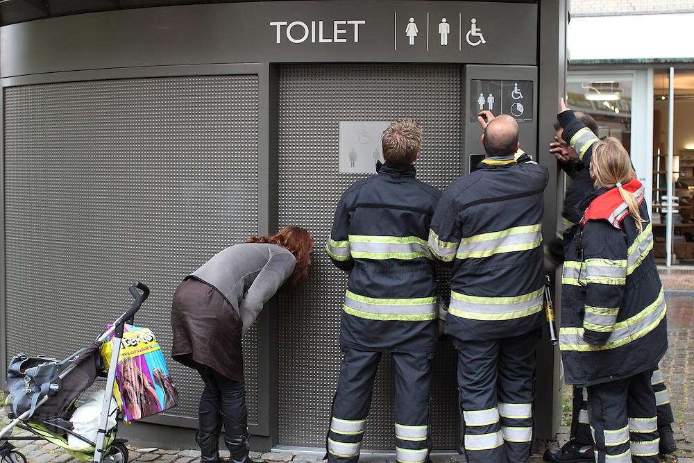 Brandweermannen zoeken naar een manier om de deur van een openbaar toilet te openen om een meisje te bevrijden. De moeder kalmeert ondertussen haar kind.<br /> <br /> Firemen are trying to open a public toilet, where a young girl has been locked up. The mother (right) is trying to calm her child.