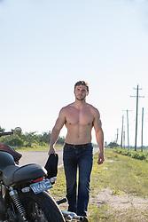 shirtless muscular man walking towards a motorcycle on a road