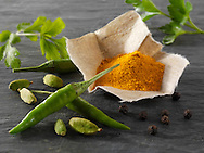 Fresh green birdseye chillies with ground turmeric & coriander leaves Indian spices
