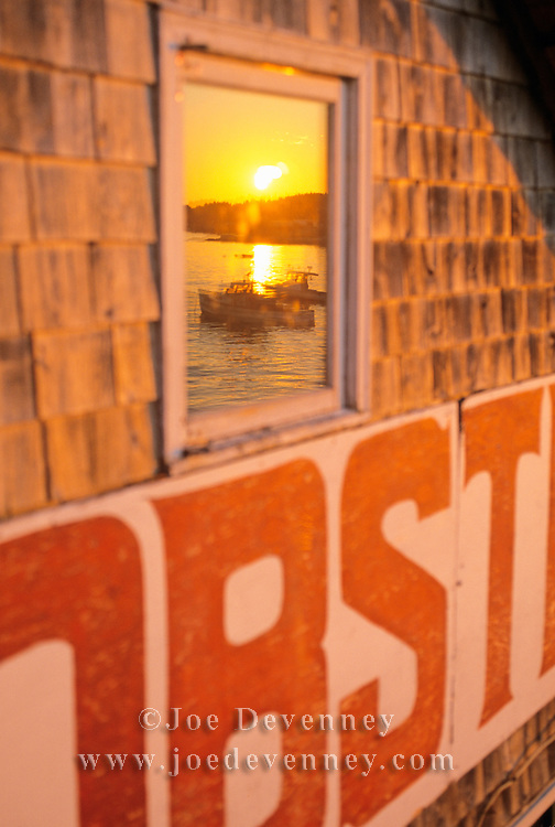Sunrise at the lobstermen's Co-Operative in Stonington, Maine. Reflections of Lobster boats in the window.