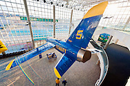 "Grumman F11(F-11) Tiger jet seen from above, with natural Sun Flare giving illusion of wing motion, suspended from Cradle of Aviation museum ceiling. ""U.S. NAVY"" printed in yellow on blue plane. Ultra wide angle view of 3 floor atrium lobby.<br />