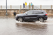 A car plows through floodwater along the Battery in the historic district as Hurricane Joaquin brings heavy rain, flooding and strong winds as it passes offshore October 4, 2015 in Charleston, South Carolina.