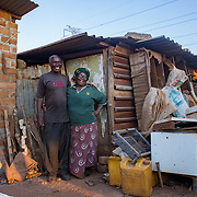 INDIVIDUAL(S) PHOTOGRAPHED: Brasford Nguluwe (left) and Theresa Nguluwe (right). LOCATION: Kuku Compound, Chitukuko, Chilanga District, Lusaka, Zambia. CAPTION: Brasford (left) and Theresa Nguluwe (right) at the home their granddaughter, Ruth Kampangele, built for them in Chitukuko, Lusaka. Ruth built their house after attending a training programme and qualifying as a bricklayer during the building of the Chitukuko Community School in 2016 as part of Build It International's Training into Work & Community Building programme. Build It International is a charity that trains unemployed young people in Zambia to become builders, while at the same time building vital schools and clinics in communities with little or nothing by way of resources.