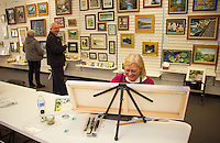 BJ Eckardt works on a painting while visitors browse the art work at NH Open Doors in conjunction with Lakes Region Art Association at the Tanger Outlet on Sunday afternoon.  (Karen Bobotas/for the Laconia Daily Sun)