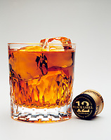 whisky glass with johnnie walker black label whisky on the rocks and bottle cap.