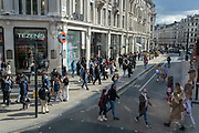 On the day that the UK government eased Covid restrictions to allow non-essential businesses such as shops, pubs, bars, gyms and hairdressers to re-open, crowds of shoppers walk across Oxford Circus, on 12th April 2021, in London, England.