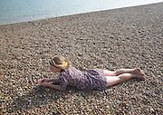 Model released young teenage girl wearing floral dress lies on shingle beach near the sea