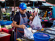 20 JUNE 2018 - BANGKOK, THAILAND: A fish monger puts a customer's order into plastic bags at Makkasan Market, a small local market in central Bangkok. Officials in Thailand are wrestling with Thais use of plastic bags. The issue became a public one in early June when a whale in Thai waters died after ingesting 18 pounds of plastic. In a recent report, Ocean Conservancy claimed that Thailand, China, Indonesia, the Philippines, and Vietnam were responsible for as much as 60 percent of the plastic waste in the world's oceans.     PHOTO BY JACK KURTZ