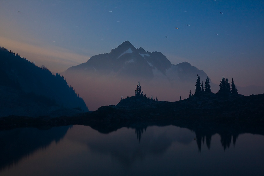 Smoke from a nearby forest fire rises over Tapto Lakes below Whatcom Peak, North Cascades National Park, Washington.