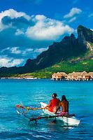Polynesian couple in an outrigger canoe in the lagoon, Four Seasons Resort Bora Bora, French Polynesia.